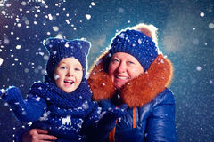 Happy grandchild and grandma having fun under the snow Stock Photo