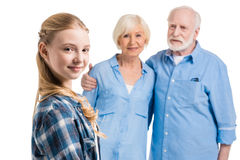 Happy grandchild looking at camera with grandfather and grandmother behind royalty free stock image
