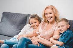 Grandchildren embracing grandmother. Happy grandchildren embracing grandmother while sitting on sofa at home royalty free stock images