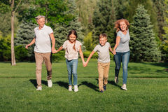 Family running on meadow royalty free stock photography