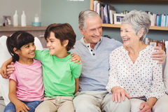 Happy grandchildren with grandparents on sofa at home Royalty Free Stock Image
