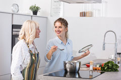 Happy granddaughter and her grandmother cooking vegetable soup Royalty Free Stock Images