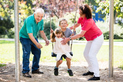 Happy Granddaughter Preparing For Swing With Their Grandparent. Senior Grandparents Having Fun With Kids On Swing In The Park Stock Photography