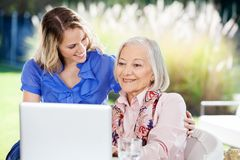 Happy Granddaughter With Senior Woman Using Laptop. Happy granddaughter looking at senior women using laptop on nursing home porch Stock Images
