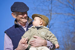 Happy grandfather. Holding cute grandson outside Royalty Free Stock Photos
