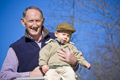 Happy grandfather. Holding cute grandson outside Stock Photos