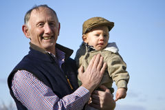 Happy grandfather. Holding cute grandson outside Stock Photo