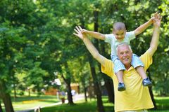 Happy grandfather and child in park Stock Images