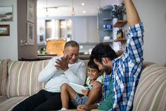 Happy grandfather and father with boy sitting on sofa Stock Images