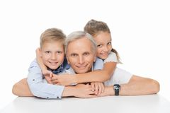 Happy grandfather with grandchildren. Hugging and smiling at camera isolated on white royalty free stock photography