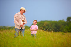 Happy grandfather with grandson having fun on summer field Royalty Free Stock Image
