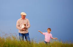 Happy grandfather with grandson having fun on summer field Royalty Free Stock Photos