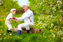 Happy grandfather and grandson playing in spring garden Stock Photo