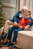 happy grandfather and grandson reading book on christmas while sitting stock image