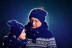 Happy grandfather and grandson talking under evening snow Royalty Free Stock Photo