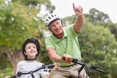 Happy grandfather with his granddaughter on their bike. On a sunny day Royalty Free Stock Images