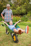 Happy grandfather and his granddaughter with a wheelbarrow Stock Images
