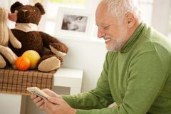 Happy grandfather looking at photo. Smiling, sitting in children room Stock Photos