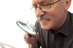 Happy grandfather looking at photo. Grandfather in his 60s with grey hair and wearing glasses looking happy examining a photo using a magnifying glass Stock Images