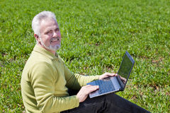 Happy grandfather with a notebook. Happy grandfather with a laptop on a grass Stock Photo