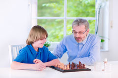 Happy grandfather playing chess with his grandson Royalty Free Stock Image