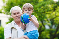 Happy grandfather playing with little grandchild ball Stock Images