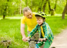 Happy grandfather teaches his grandson to ride a bike.  royalty free stock image