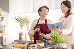 Happy grandma cooking. With her granddaughter in modern kitchen royalty free stock images