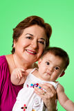 Happy grandma and cute baby. Beautiful happy senior Caucasian Hispanic Latina grandmother holding cute baby in arms, on a green background Royalty Free Stock Images