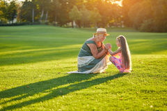 Happy grandma with granddaughter. People and green grass. Kids are the future royalty free stock images