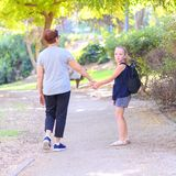 Happy Grandma and granddaughter walking to school on the street in the autumn park. stock photo