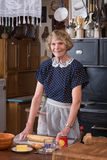 Happy Grandma. A happy grandmother making a pie in clothing and kitchen in the 1940's stock images