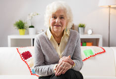 Happy grandma sitting on the couch Royalty Free Stock Images