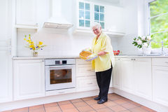 Happy grandmother baking a pie in a white kitchen. Beautiful fir and active senior lady baking a delicious apple pie in a sunny kitchen with modern furniture and Stock Photo