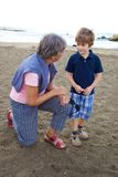 Happy grandmother chatting with grandson on a beach Stock Photography