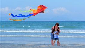 Happy grandmother with child the playing flying kite, the family runs on the sand of a tropical ocean playing with the