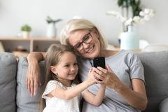 Happy grandmother and cute granddaughter using cellphone making. Happy grandmother and cute granddaughter using cellphone together, smiling older grandma and royalty free stock photography