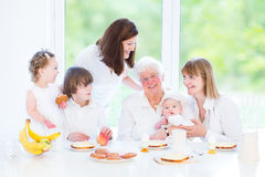 Happy grandmother enjoying breakfast with her family Stock Image
