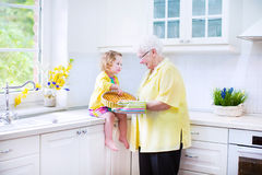 Happy grandmother and girl baking pie in white kitchen. Happy beautiful great grandmother and her adorable granddaughter, curly toddler girl in colorful dress Royalty Free Stock Image