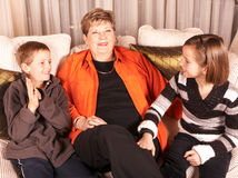 Happy grandmother and grandchildren on sofa. Mature Caucasian woman, boy and girl sit close together on sofa and laugh Royalty Free Stock Photo
