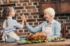 Happy grandmother and granddaughter giving high five on thanksgiving after successful. Turkey cooking stock photos