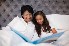 Happy grandmother and granddaughter reading book on bed. At home Stock Image