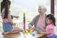 Happy grandmother and granddaughters playing with alphabet blocks at table Royalty Free Stock Photo