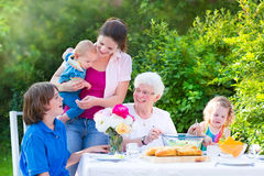 Happy grandmother having lunch with her family. Happy grandmother enjoying a sunny summer day having lunch with her family - young women and three children, teen Royalty Free Stock Images