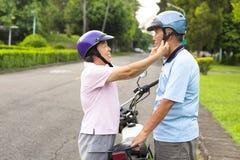 Happy grandmother help grandfather to wear a helmet Stock Photo