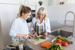 Happy grandmother and her granddaughter cooking together Stock Photos