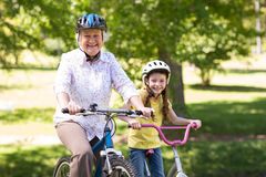 Happy grandmother with her granddaughter on their bike Stock Photography