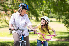 Happy grandmother with her granddaughter on their bike Royalty Free Stock Image