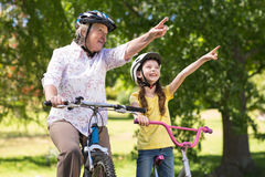 Happy grandmother with her granddaughter on their bike Royalty Free Stock Images