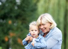 Happy grandmother holding baby girl outdoors Royalty Free Stock Images